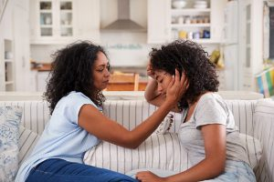 Mom talking to emotional teenage daughter